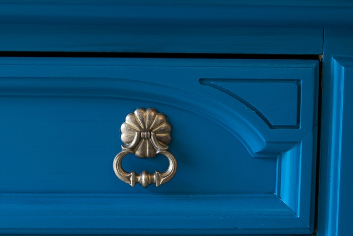 picture of section of drawer painted teal and gold hardware