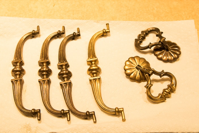 picture of brass hardware with two pieces fully restored to shiny gold finish