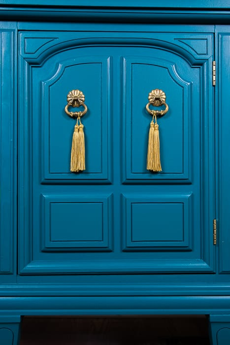 picture of teal dresser door with gold hardware and gold tassels