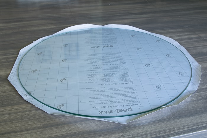 picture showing round glass top with shelf paper cut to size with 1 inch overhang