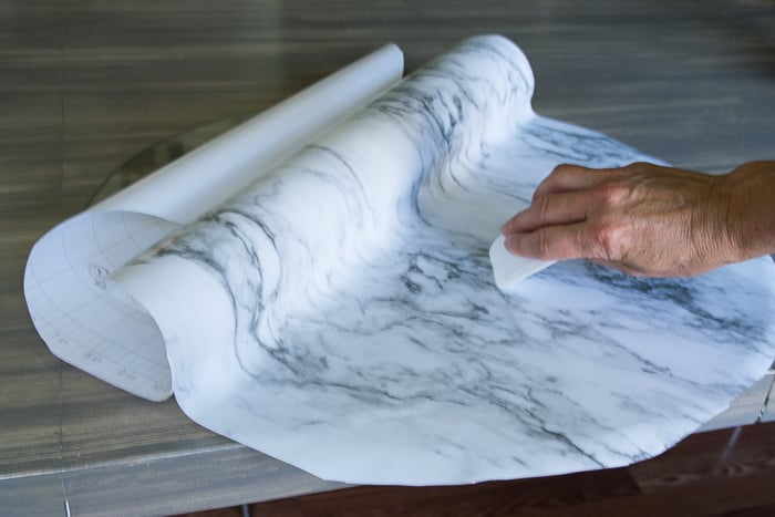 picture showing marble shelf liner paper applied to table round with plastic dough scraper