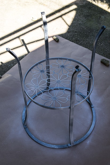 picture of black metal table upside down with primer coat sprayed on