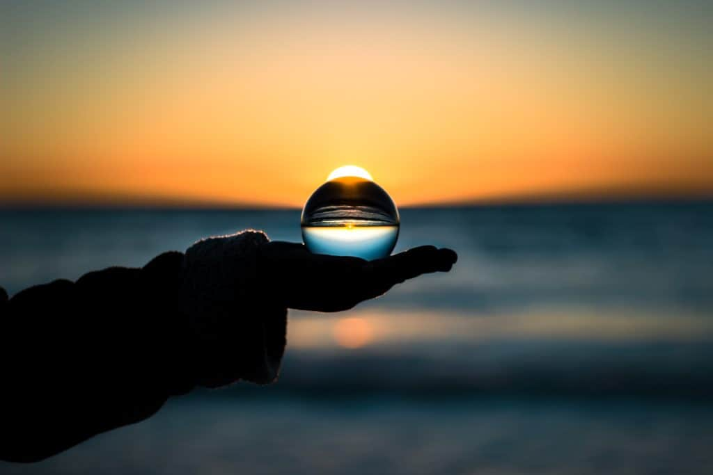 picture of hand holding a glass ball in front on rising sun