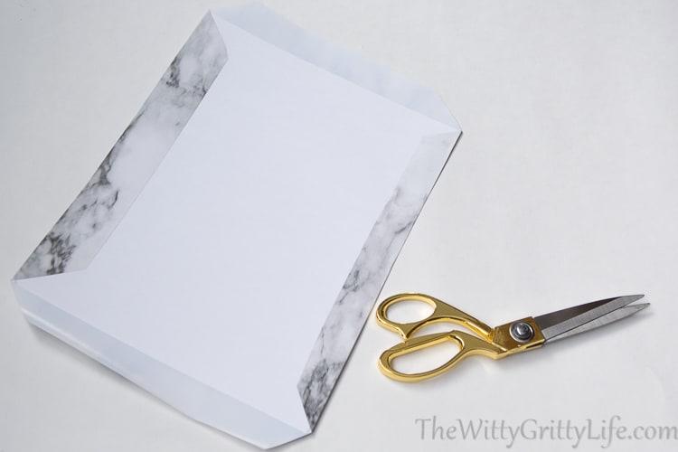 picture of scissors, cardboard with shelf liner folded onto cardboard