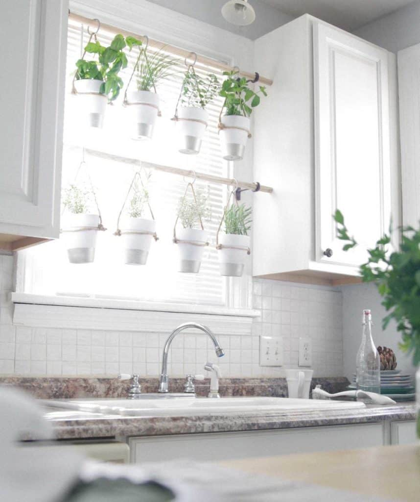picture of herb pots hanging from rods in a kitchen window