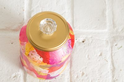 top view of a multi color decoupaged jar with a golden lid and a crystal knob