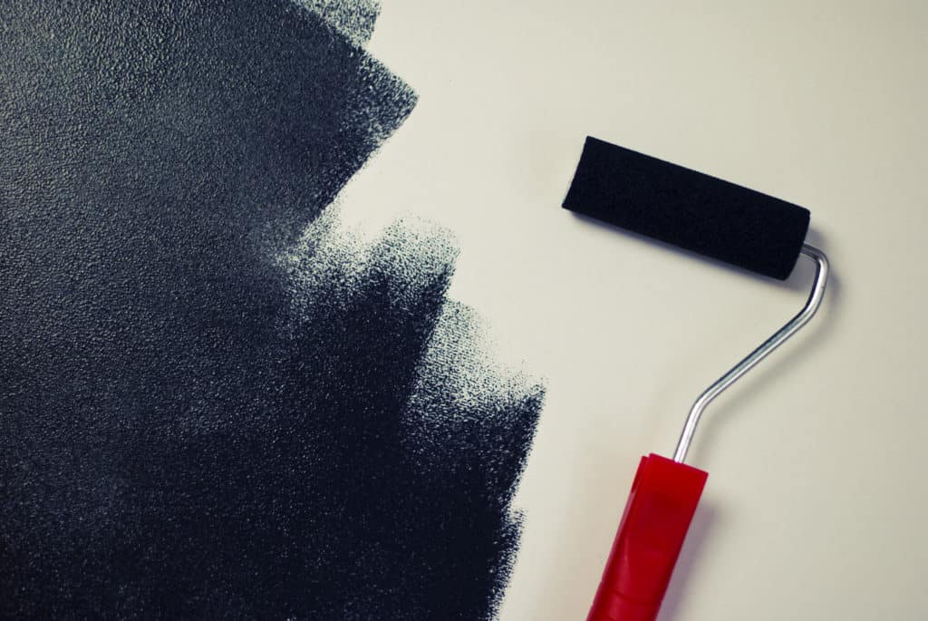 roller with black paint on white background