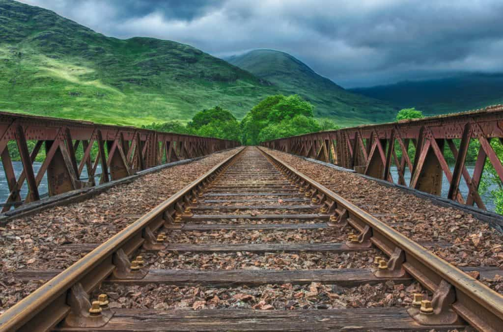 railroad tracks leading to beautiful green mountains
