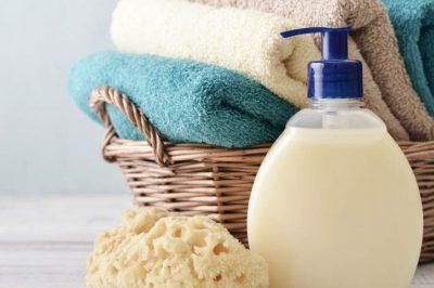 make liquid soap, soap dispenser, basket of towels and sponge