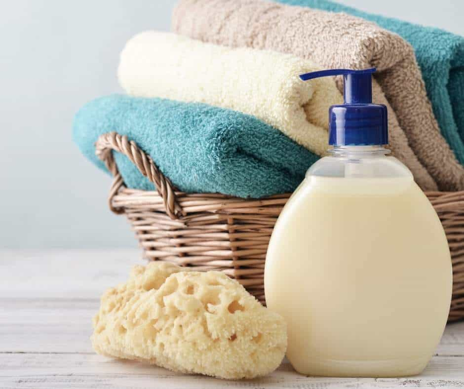 make liquid soap, soap dispenser, basket of towels and sponge