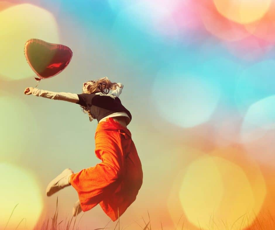 woman jumping into the air holding a heart shaped balloon in front of a colorful background