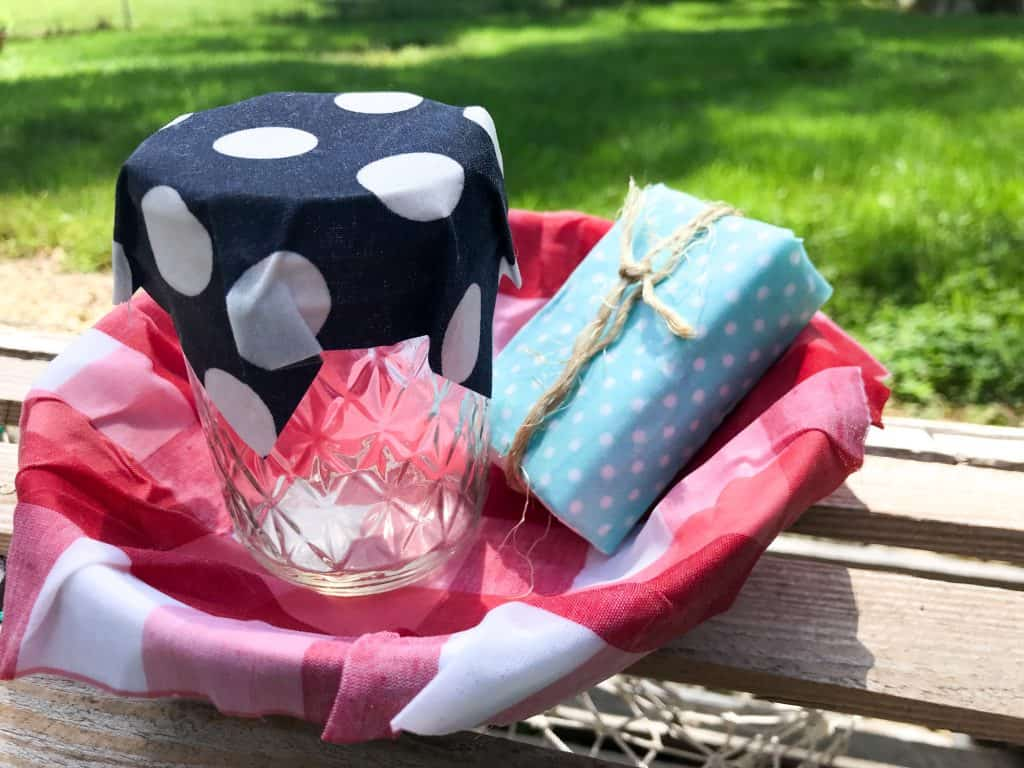 picture showing a bowl lined with red and white checker fabric holding a jar with blue and white polka dot cover and a bar of soap wrapped in light blue fabric and twine