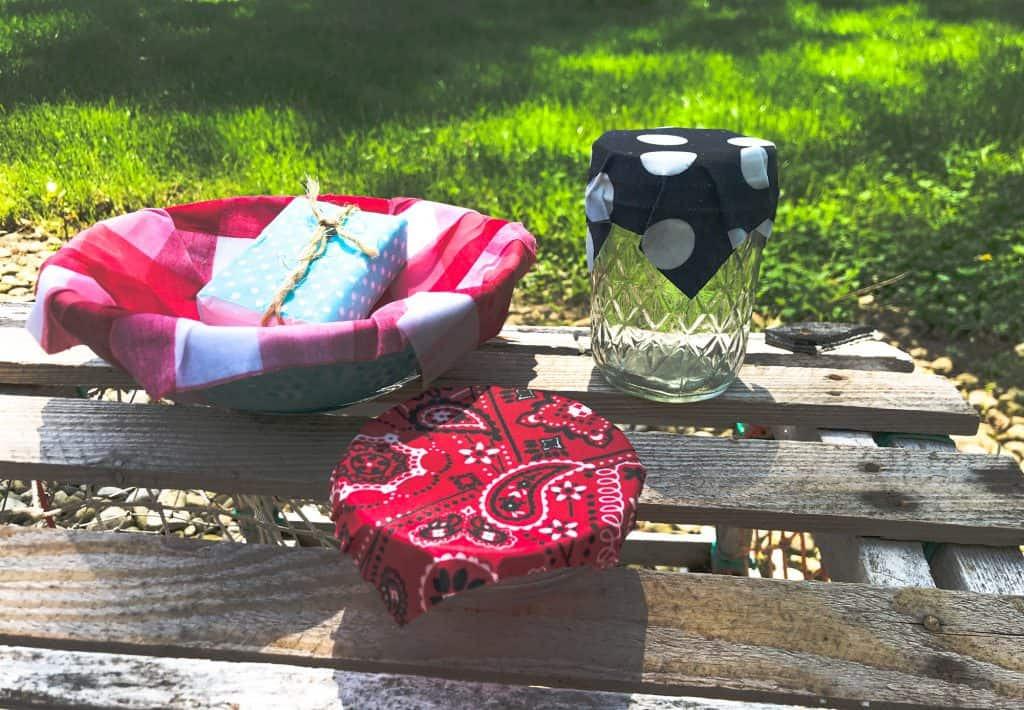 picture showing wax fabric lined bowl, small bowl covered in waxed bandana fabric, bar of soap wrapped in wax fabric and jelly jar with blue and white ploka dot cover