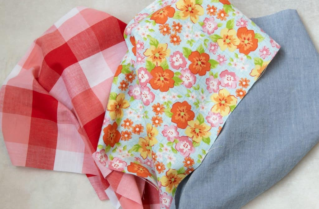 Three different fabrics from left to right: red and white checker, orange and light blue flower, chambray