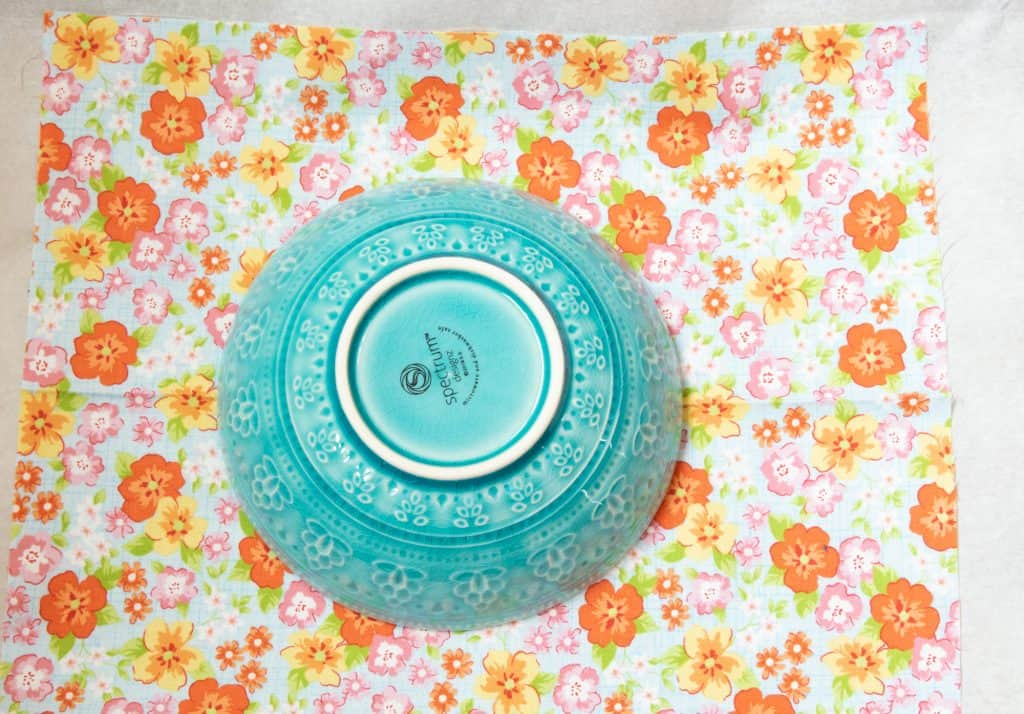 picture of light blue bowl upside down on orange and light blue floral fabric