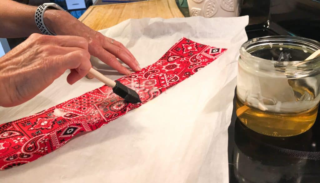 picture showing hand holding a foam craft brush and brushing on melted wax on a piece of red bandana fabric