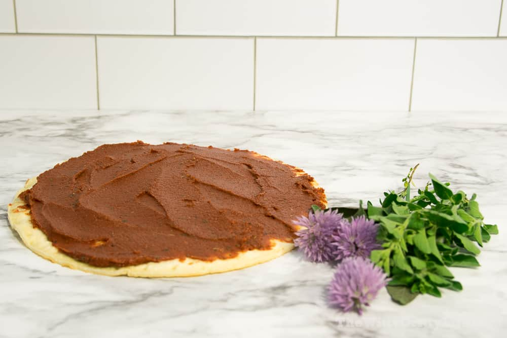 pizza crust with sauce on top and fresh herbs next to it