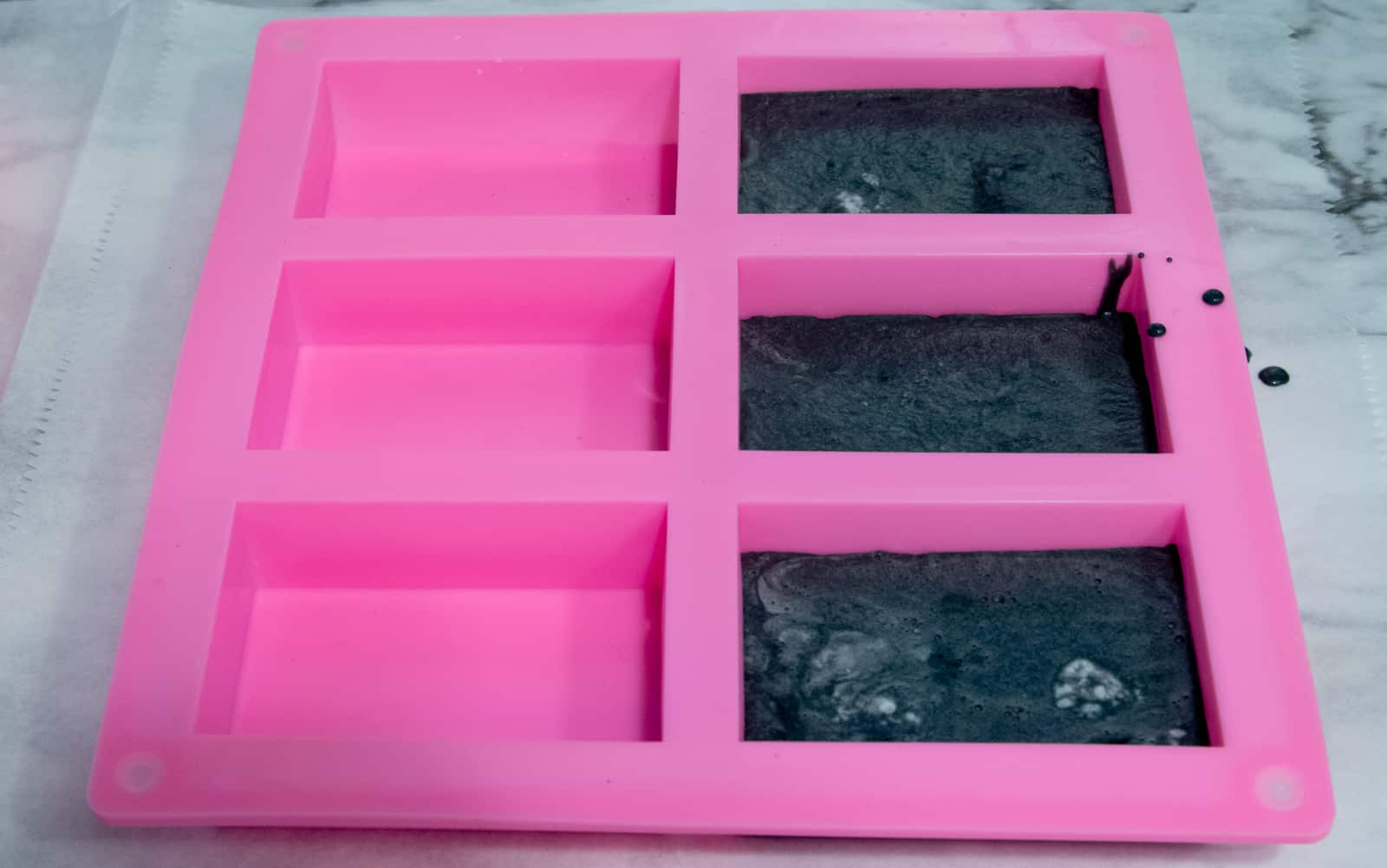 silicone molds partially filled with activated charcoal soap mixture
