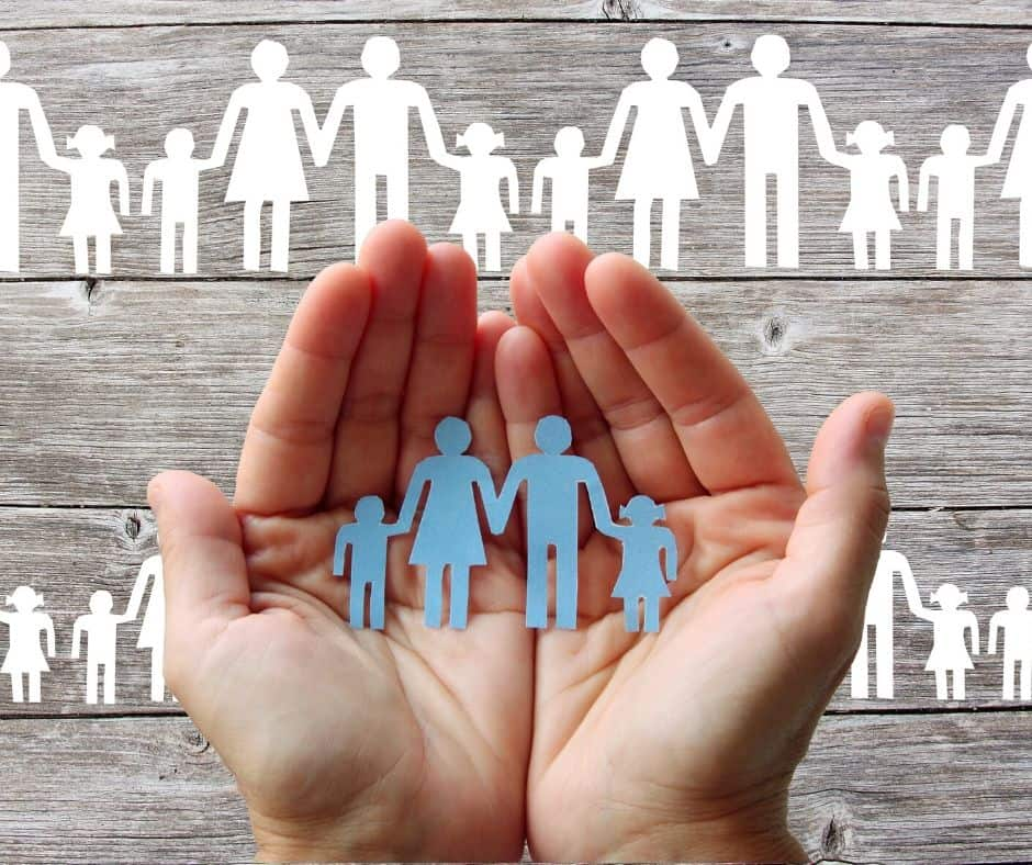hands holding paper silhouette of family