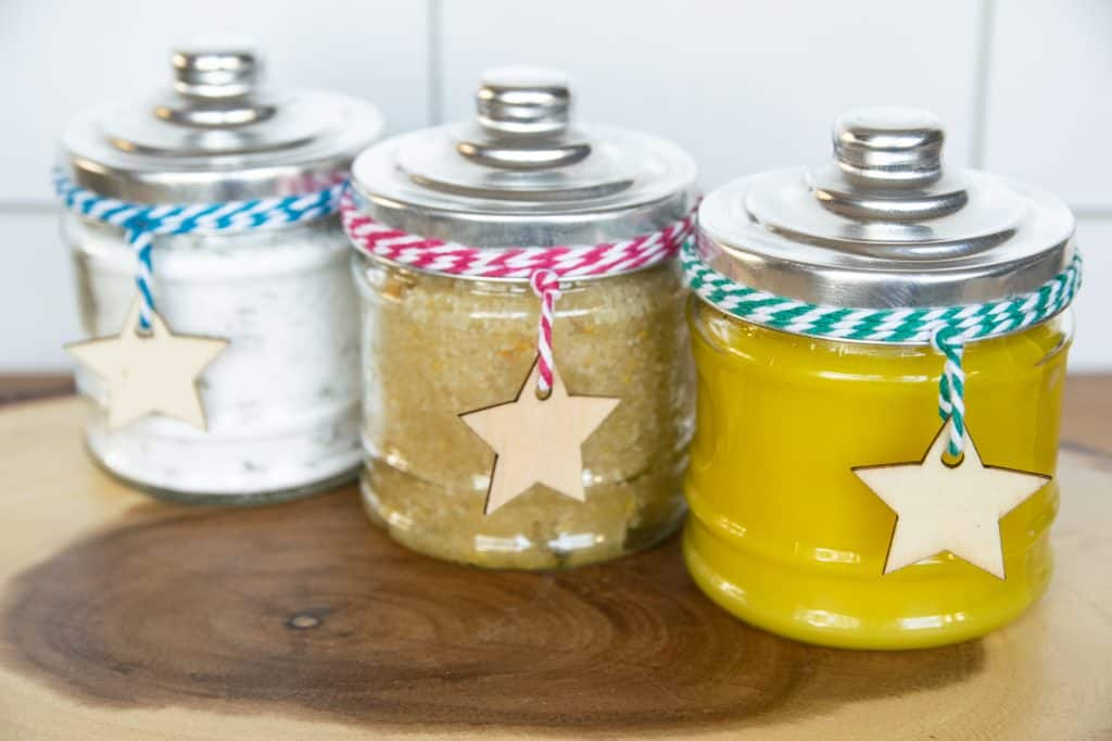image showing three identical glass jars with colorful string and wood stars each containing a different homemade bodycare product