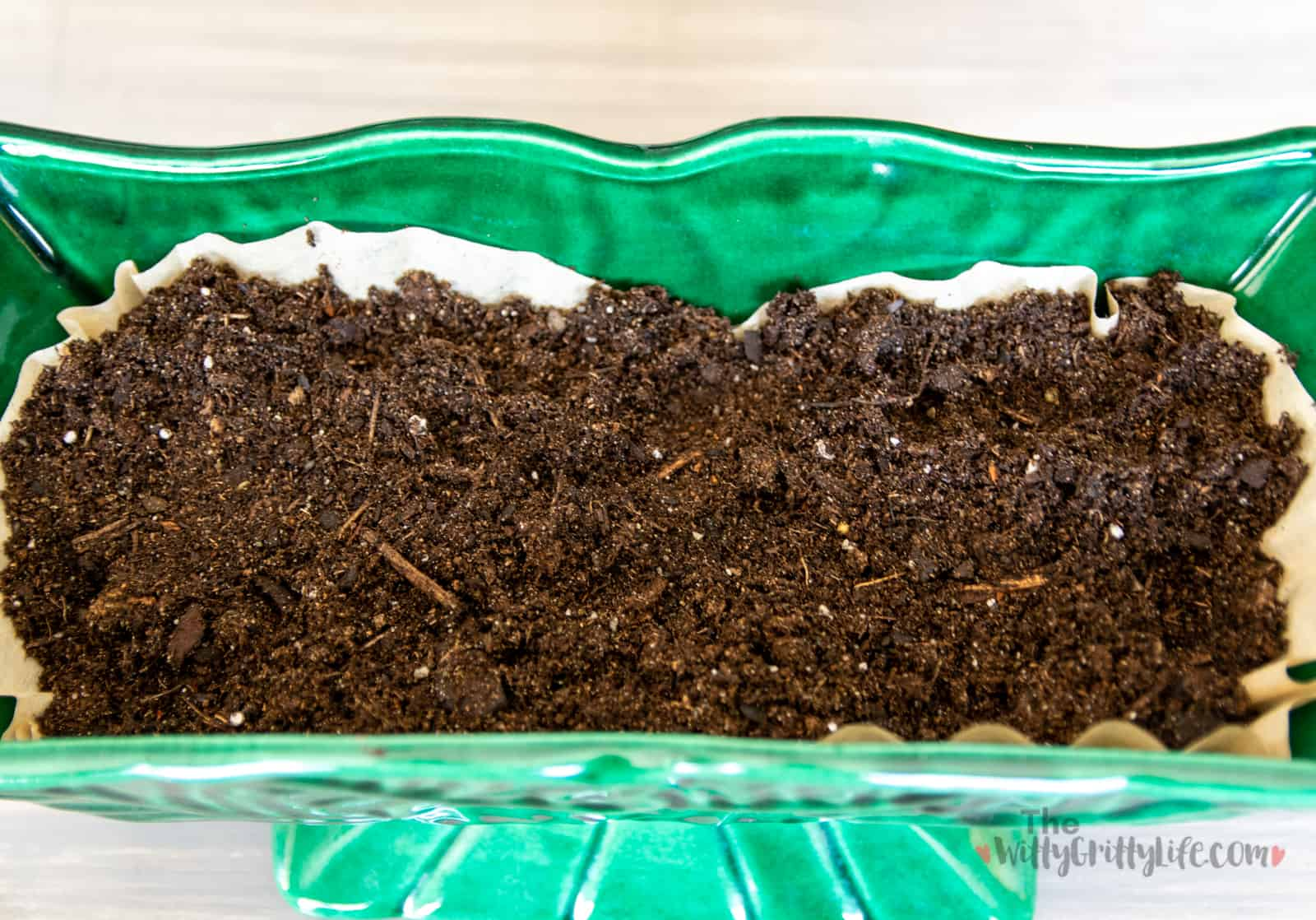 planter with potting soil on top of drainage pebbles and coffee filters