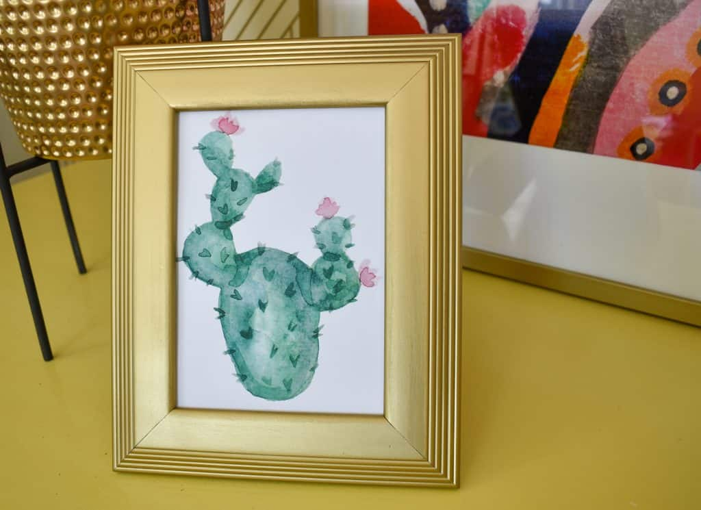 image showing watercolor print of a cactus in a gold frame