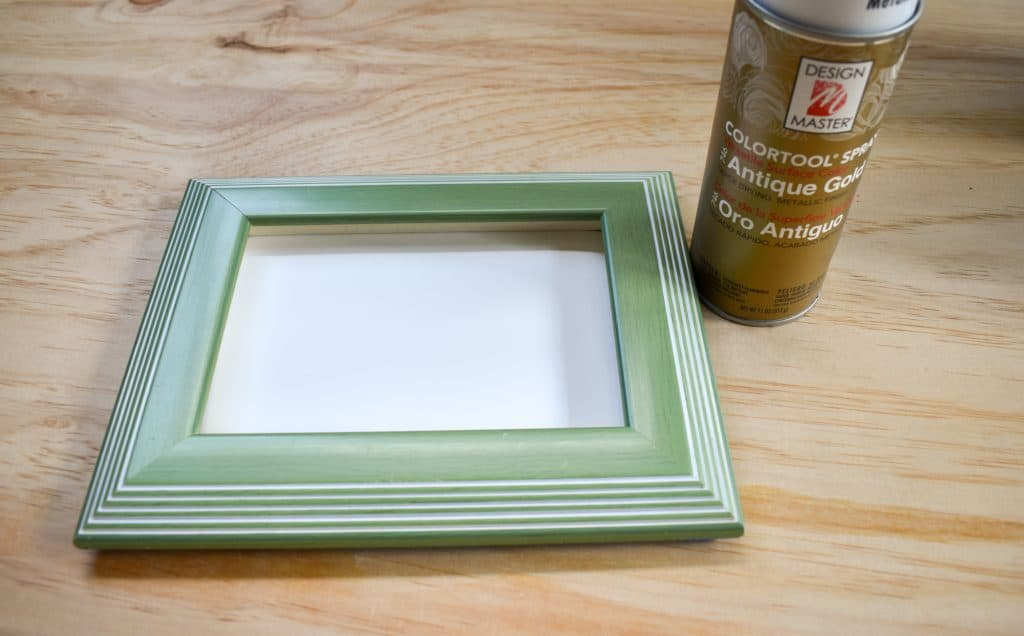 image showing light green picture frame and gold spray paint can on a wood background