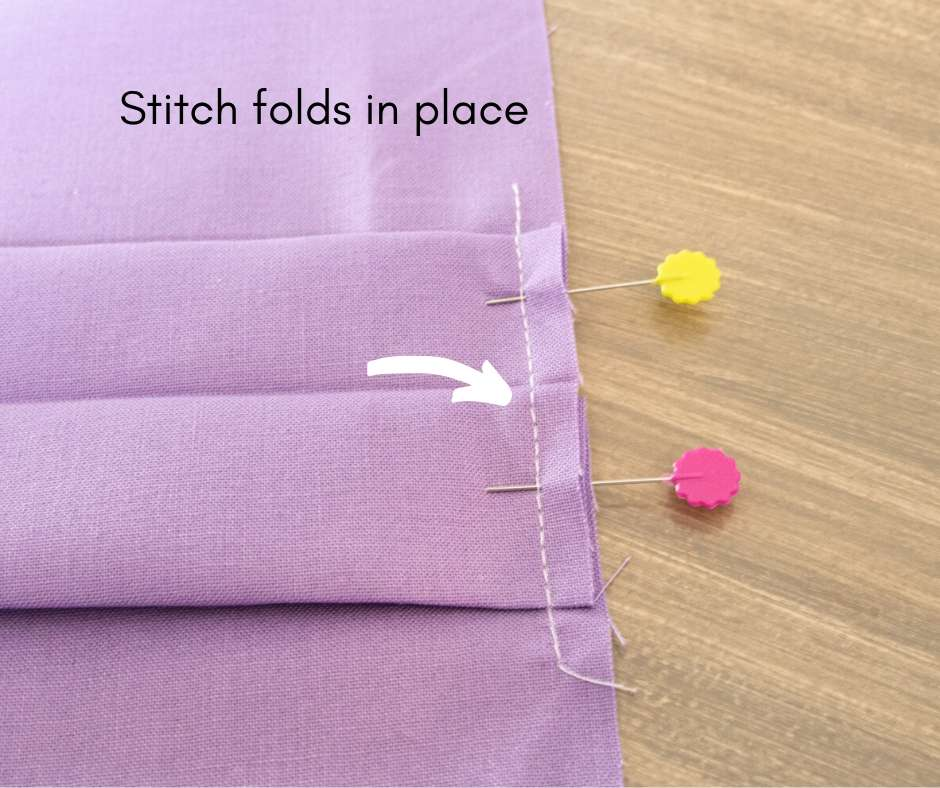 image showing centerfold stitched with 2 pins still in place and arrow pointing toward stitch line