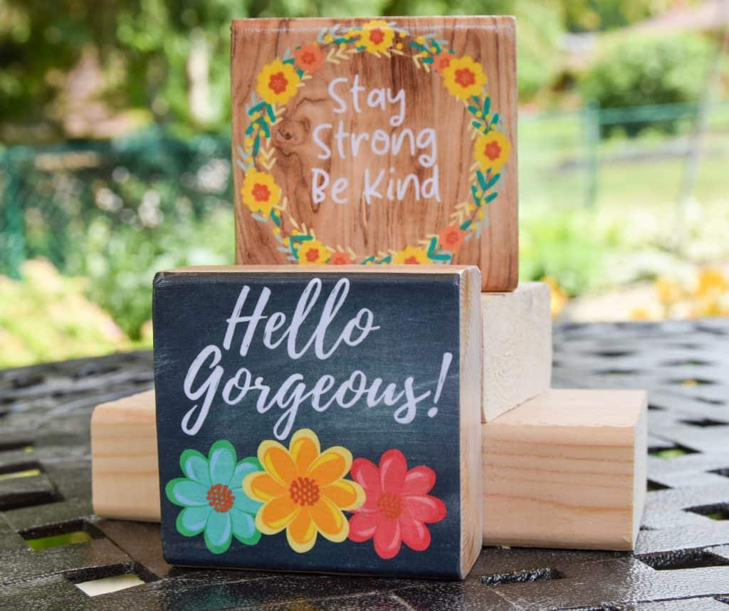 image with wooden blocks one with chalkboard background and flowers stating: hello gorgeous the other featuring a flower wreath and quote: stay strong be kind