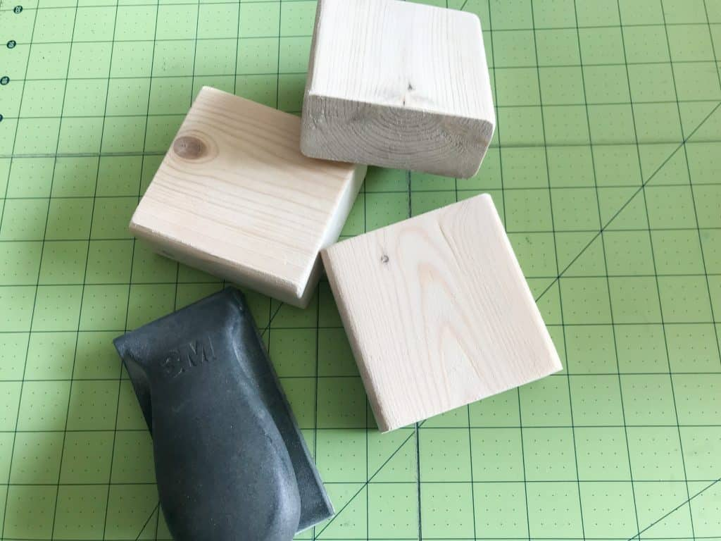 image of three small square wood blocks and sanding tool on a lined cutting mat