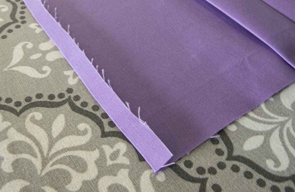 image showing seam rolled up and pressed on one end of fabric for  washable face mask